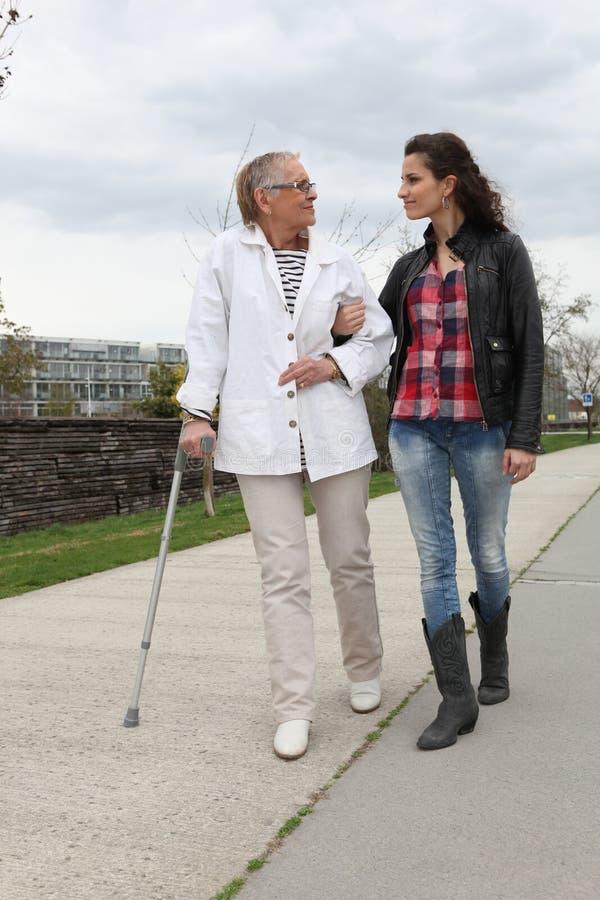 Frau, die eine ältere Dame unterstützt lizenzfreie stockfotografie
