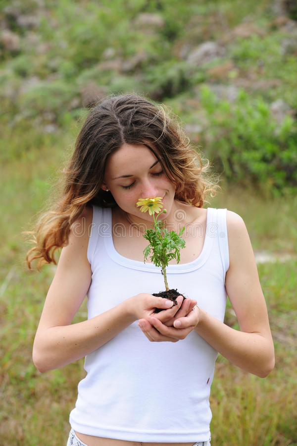 Frau, die eine Blume riecht lizenzfreies stockfoto