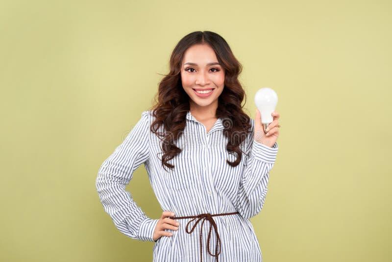 Frau, die eine energiesparende Glühlampe - lokalisiert über Grün hält stockfotografie