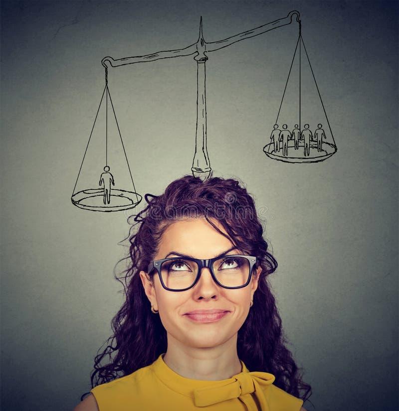 Frau, die eine Entscheidung mit Skala über Kopf und Leuten auf einer Balance trifft lizenzfreie stockbilder