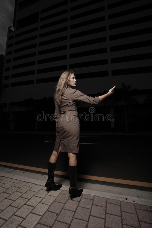 Frau, die eine Fahrt in der Dunkelheit hitching ist lizenzfreies stockbild