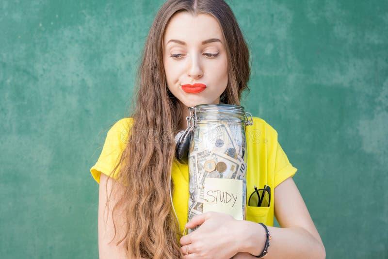 Frau, die eine Flasche voll von den Geldeinsparungen für Studie hält lizenzfreies stockfoto