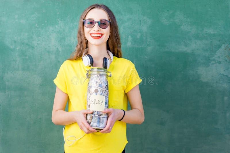 Frau, die eine Flasche voll von den Geldeinsparungen für Studie hält stockbild