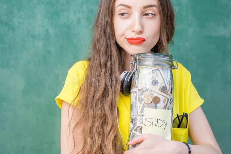 Frau, die eine Flasche voll von den Geldeinsparungen für Studie hält stockfotos