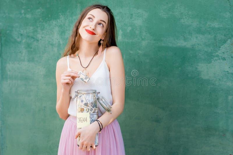 Frau, die eine Flasche voll von den Geldeinsparungen hält lizenzfreie stockbilder