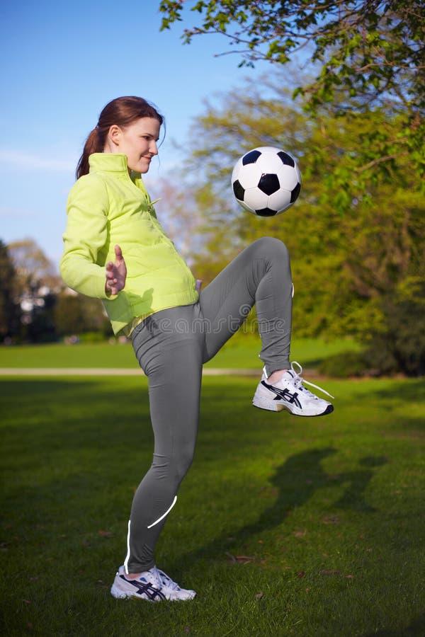 Frau, die eine Fußballkugel tritt stockfotografie