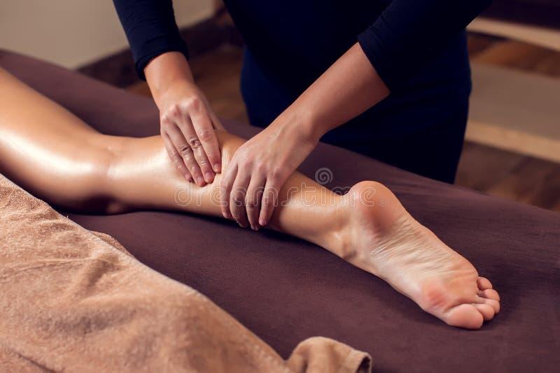 Frau, die eine Fußmassage am Badekurortsalon empfängt und genießt lizenzfreies stockbild