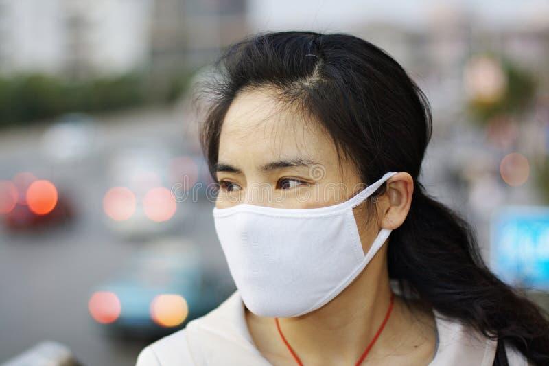 Frau, die eine Gesichtsmaske trägt lizenzfreies stockfoto