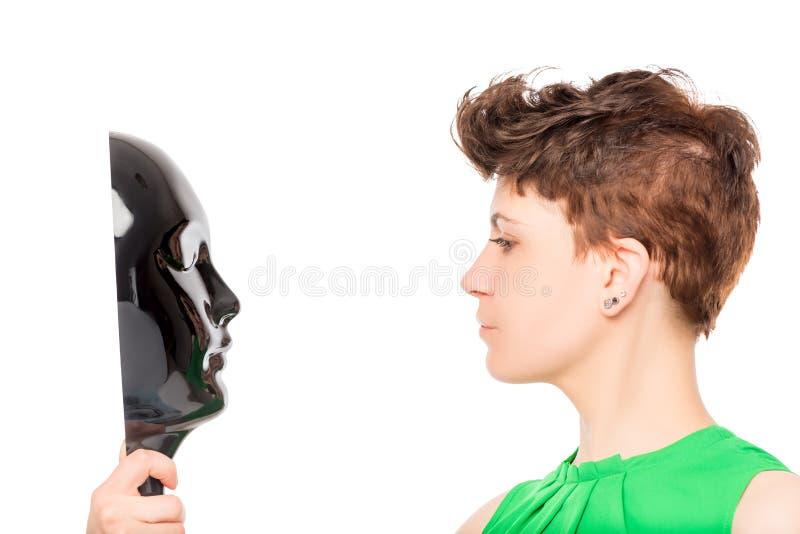 Frau, die eine glatte schwarze Maske auf einem Weiß betrachtet stockbilder