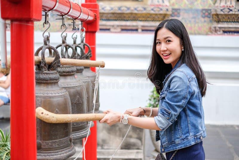 Frau, die eine Glocke in einem buddhistischen Tempel schellt lizenzfreie stockbilder