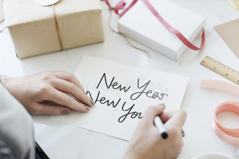 Frau, die eine guten Rutsch ins Neue Jahr-Karte schreibt stockbild