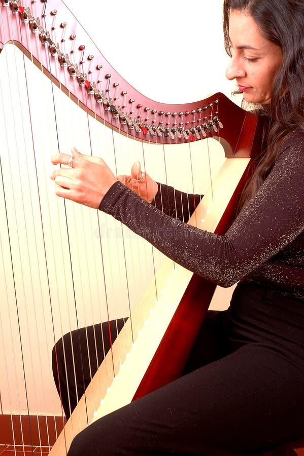 Frau, die eine Harfe spielt lizenzfreie stockbilder
