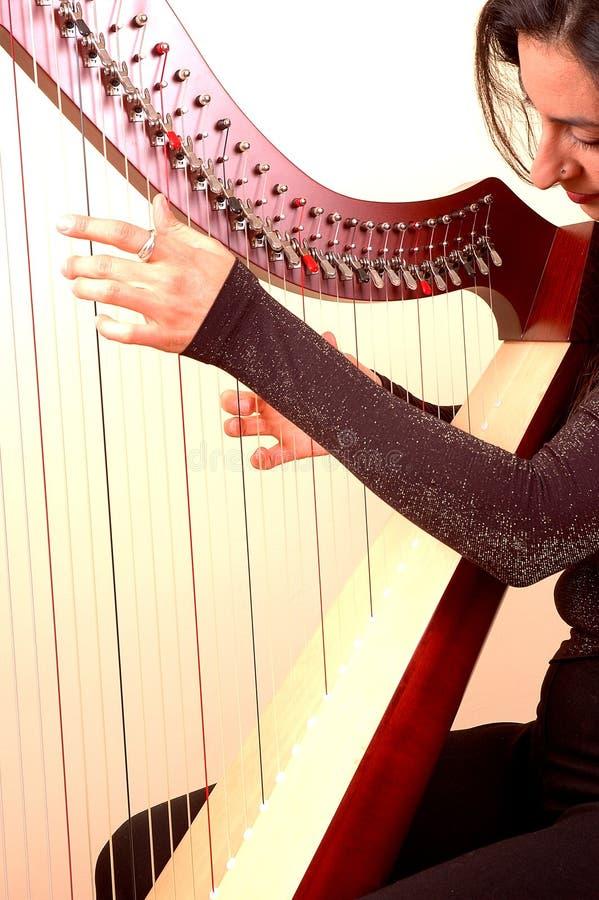 Frau, die eine Harfe spielt lizenzfreies stockbild