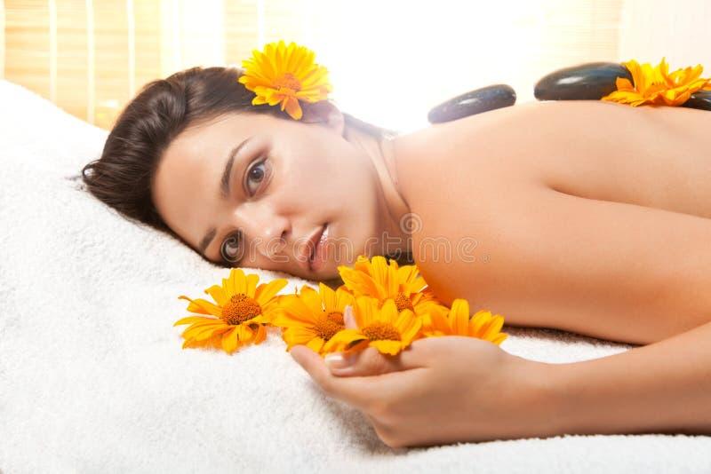 Frau, die eine heiße Steinmassage am Badekurortsalon erhält stockbild