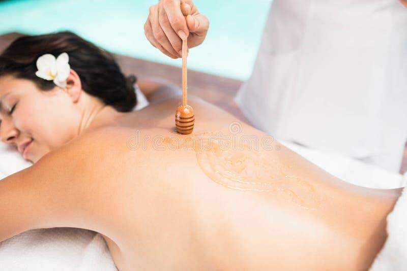 Frau, die eine Honigmassage vom Masseur empfängt lizenzfreies stockbild