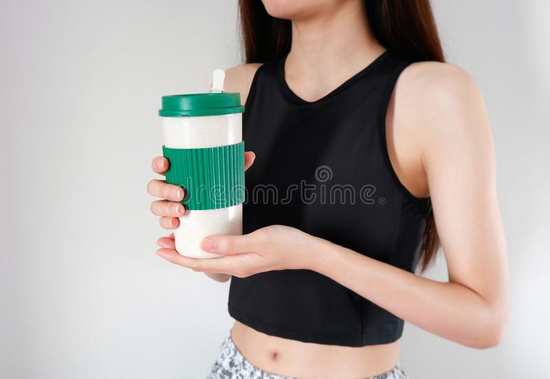 Frau, die eine Kaffeetasse in den H?nden mit ?bungsm?dchenhintergrund h?lt Leerer Becher f?r Entwurf stockfotografie