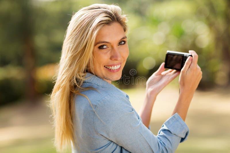 Frau, die eine Kamera hält stockbilder