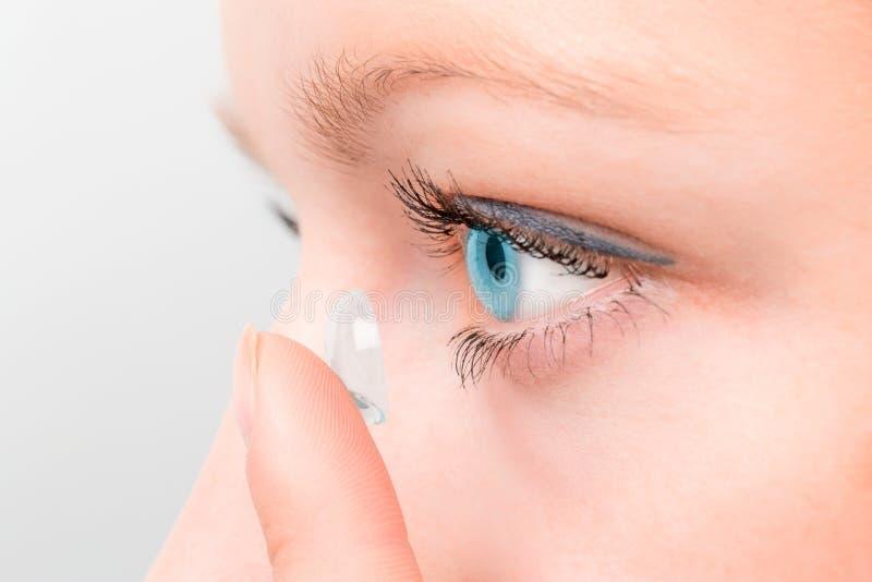 Frau, die eine Kontaktlinse in Auge einfügt stockfotografie