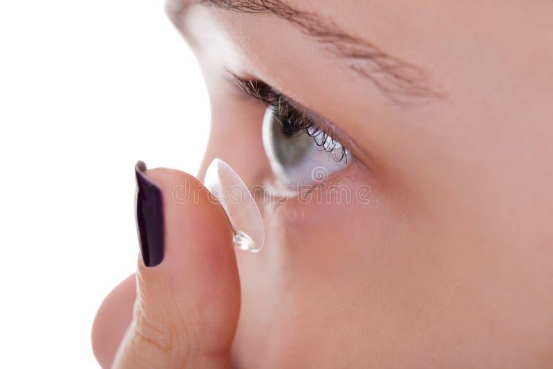 Frau, die eine Kontaktlinse einsteckt lizenzfreie stockfotos