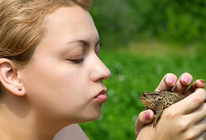 Frau, die eine Kröte küßt lizenzfreie stockbilder