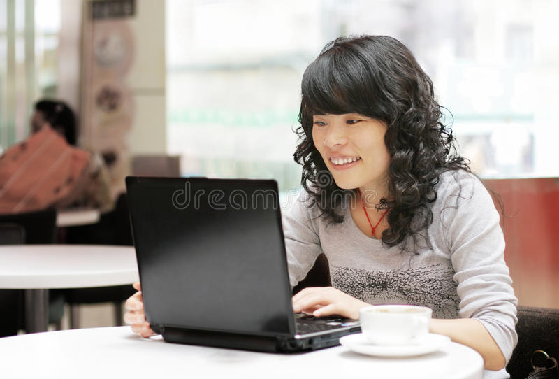 Frau, die eine Laptop-Computer verwendet lizenzfreies stockbild