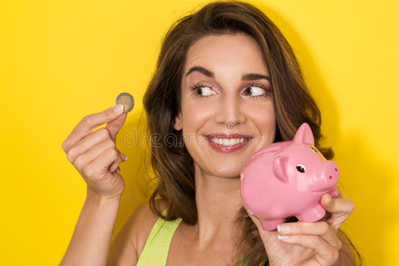 Frau, die eine Münze in kleines Sparschwein einsetzt lizenzfreie stockfotografie