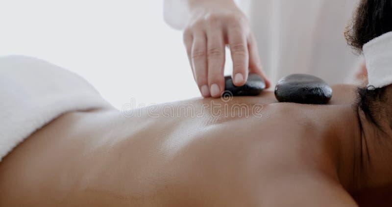 Frau, die eine Massage mit heißem Stein empfängt stockfoto