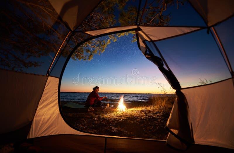 Frau, die eine Nachtzeit kampiert nahe touristischem Zelt, Lagerfeuer auf Seeufer unter sternenklarem Himmel hat lizenzfreies stockbild