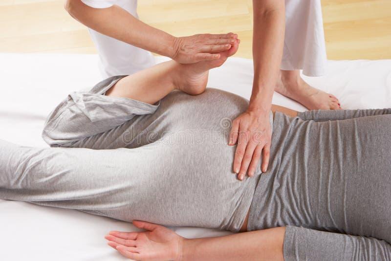 Frau, die eine niedrigere rückseitige Massage hat lizenzfreie stockfotografie