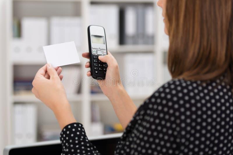 Frau, die eine Nummer auf einer Visitenkarte wählt lizenzfreie stockfotografie