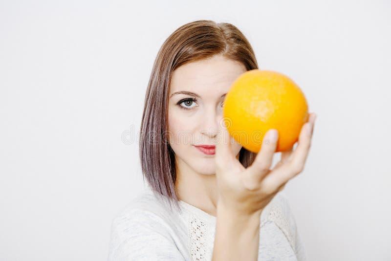 Frau, die eine Orange anhält Orange auf dem Mädchen ` s Kopf stockfoto