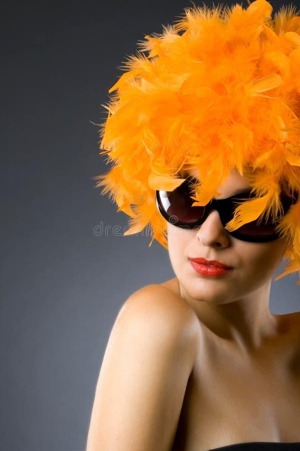 Frau, die eine orange Federperücke und -sonnenbrillen trägt stockfotografie