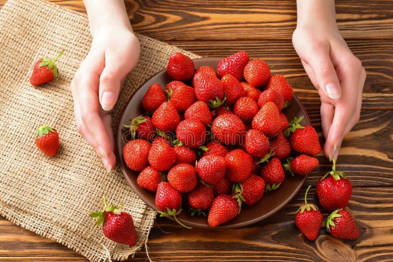 Frau, die eine Platte von Erdbeeren hält lizenzfreie stockfotografie