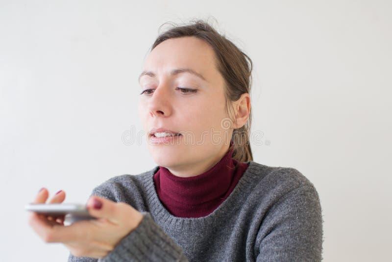 Frau, die eine Sprachmassage am Telefon lässt stockfotografie