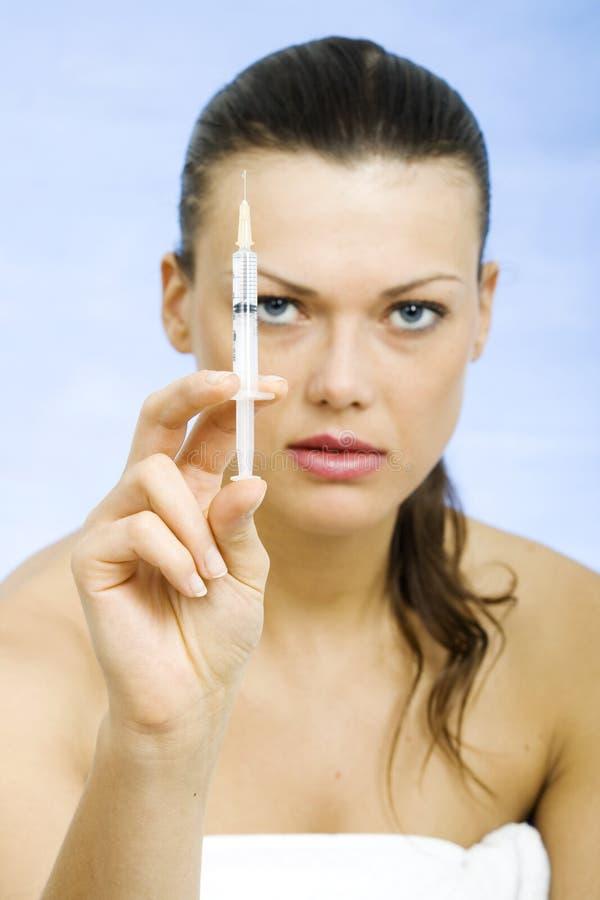 Frau, die eine Spritze bereit zur Gesichtskosmetikbehandlung hält lizenzfreie stockbilder