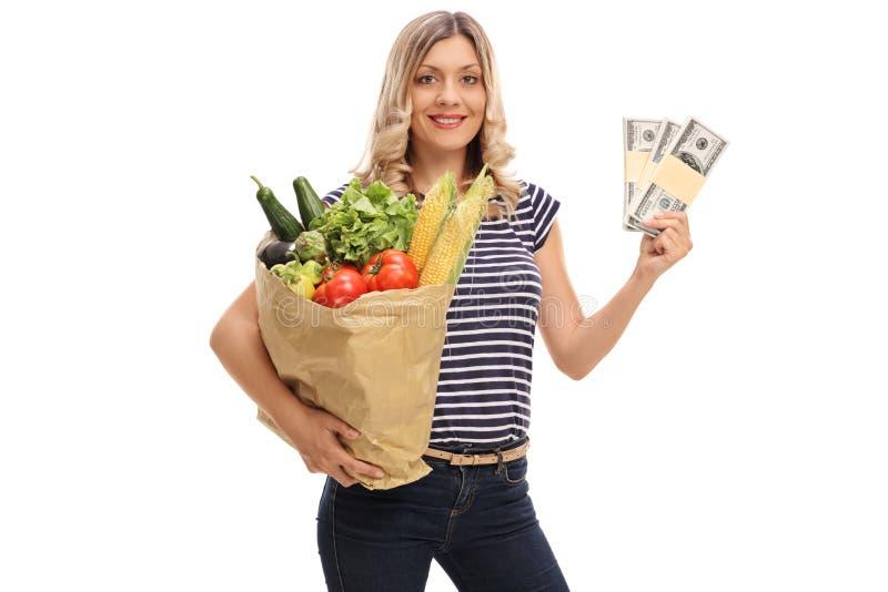 Frau, die eine Tasche von Lebensmittelgeschäften und von Stapeln Geld hält stockfoto