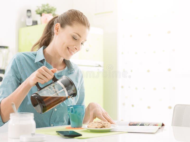 Frau, die eine Tasse Tee isst stockbild
