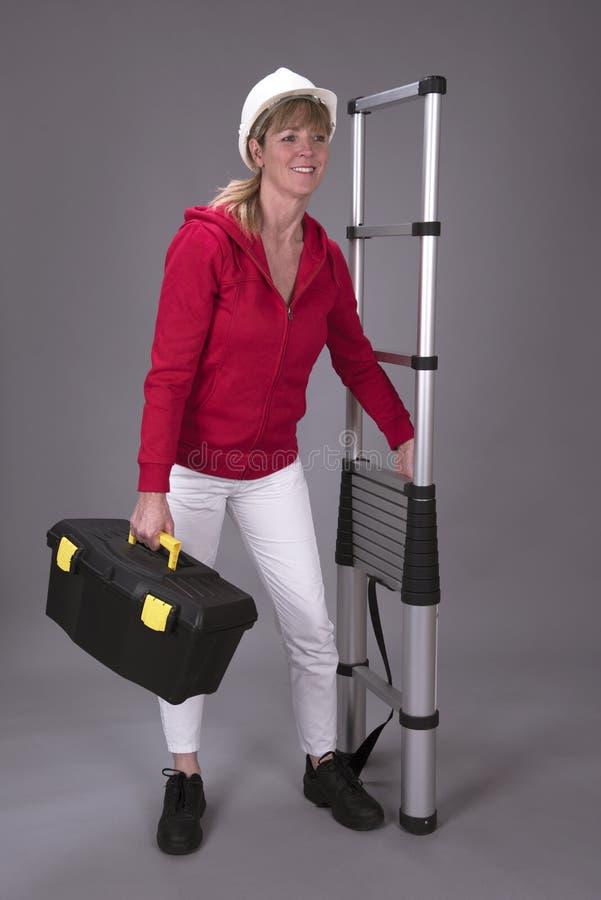 Frau, die eine teleskopische Leiter und einen Werkzeugkasten hält stockfotos
