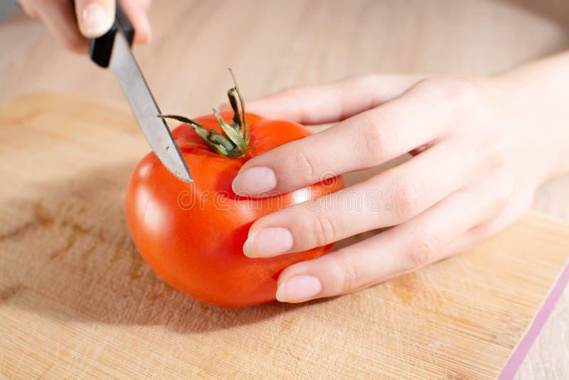 Frau, die eine Tomate auf dem hölzernen geschnittenen Brett schneidet stockfotos