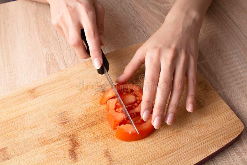 Frau, die eine Tomate auf dem hölzernen geschnittenen Brett schneidet lizenzfreie stockfotografie