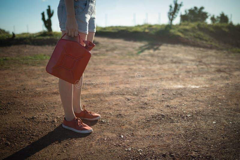 Frau, die eine Treibstoffdose hält stockfotos