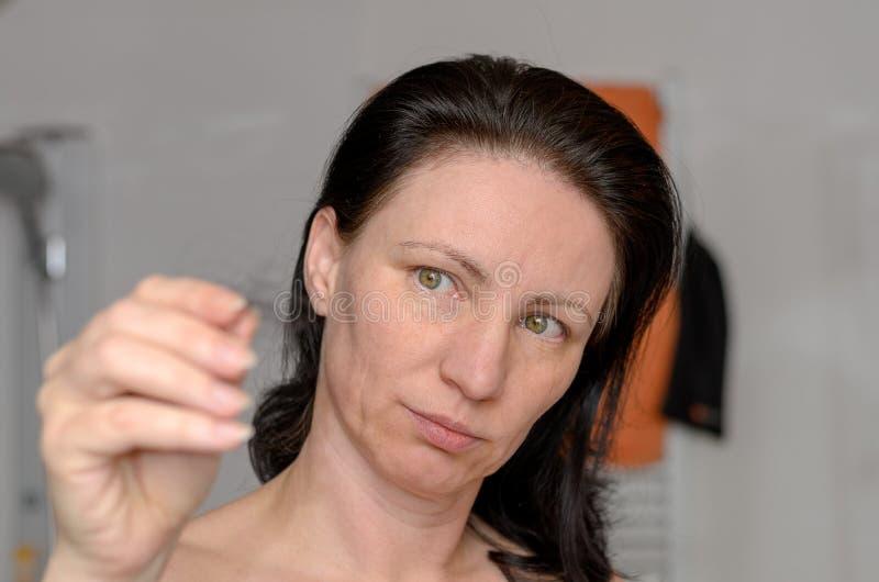 Frau, die eine Verwicklung des Haares in ihren Fingern hält stockfotos