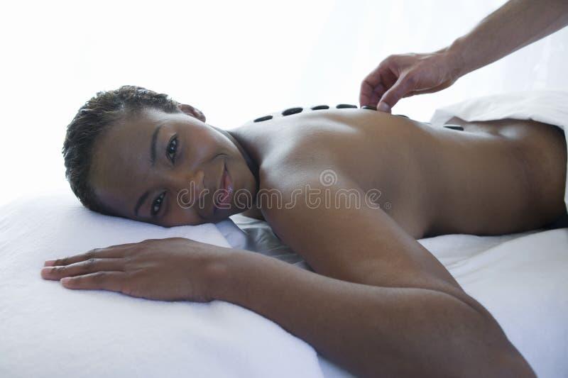 Frau, die eine Warmsteinmassage am Badekurort erhält stockbild