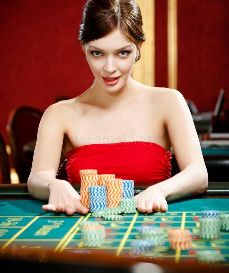 Frau, die eine Wette am Kasino platziert lizenzfreies stockfoto