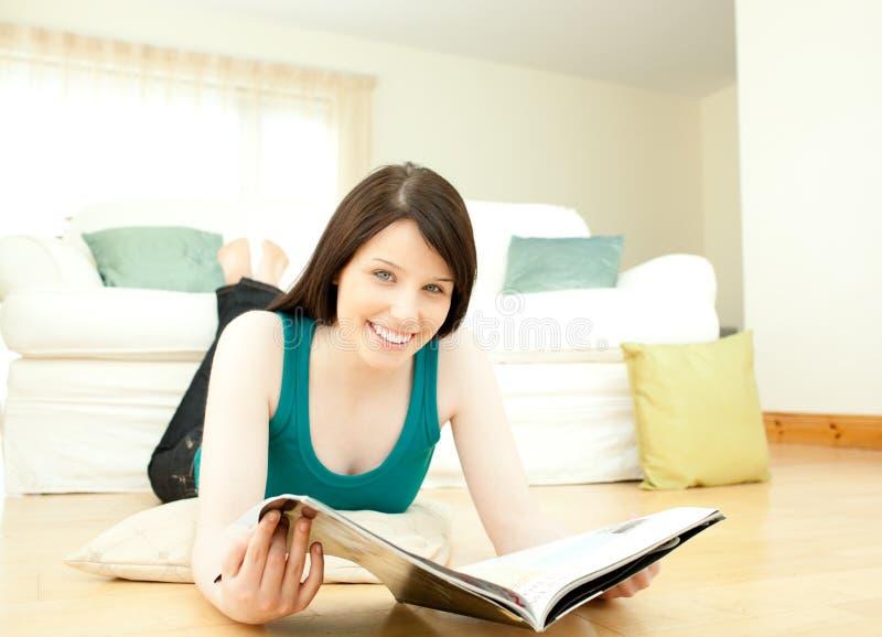 Frau, die eine Zeitschrift sich hinlegt auf dem Fußboden liest lizenzfreies stockbild