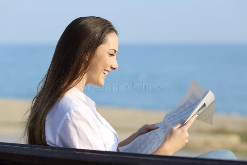 Frau, die eine Zeitung sitzt auf einer Bank auf dem Strand liest stockbild