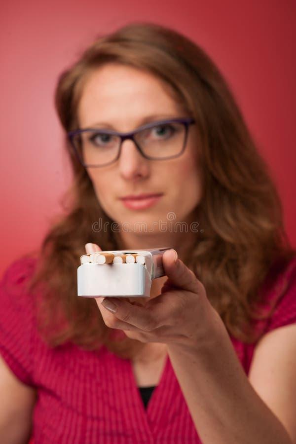Frau, die eine Zigarette anbietet stockfoto