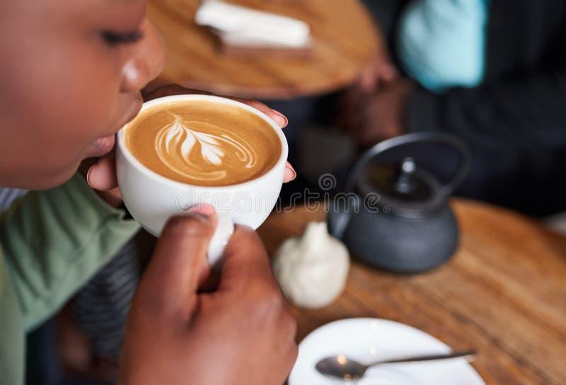 Frau, die an einem Cafétisch trinkt ihren Cappuccino sitzt stockfotografie