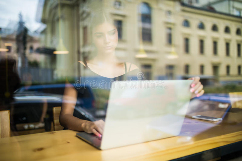 Frau, die an einem Computer an einem Café während Blick durch das Fensterglas arbeitet stockbilder