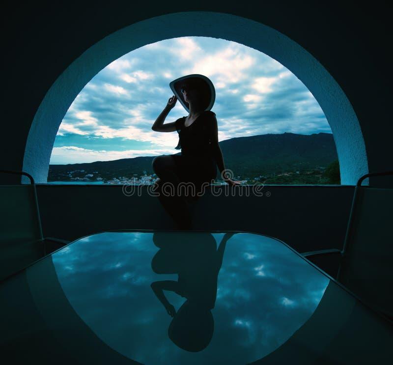 Frau, die in einem Fenster sitzt lizenzfreies stockfoto